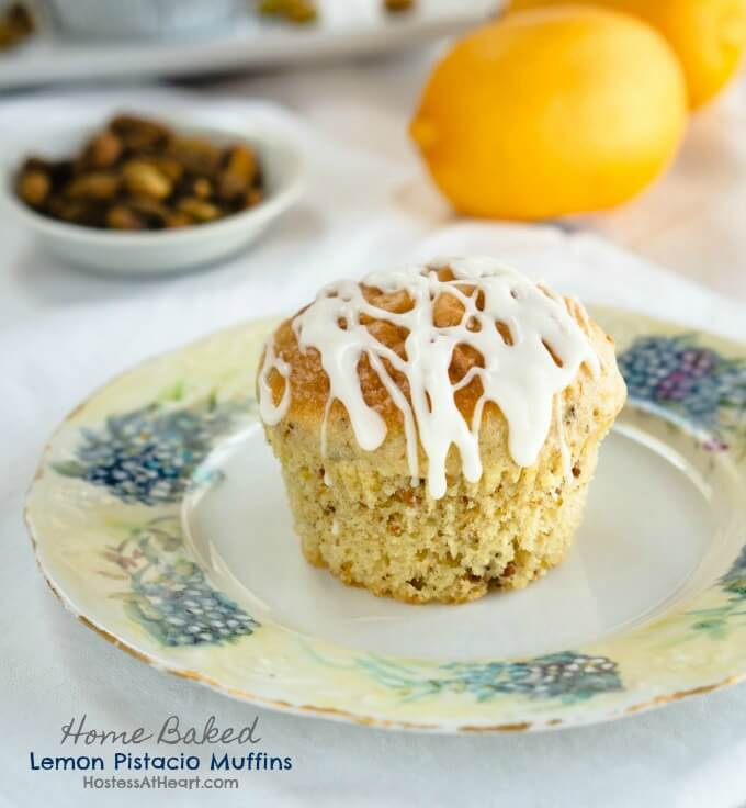 Soft and tender lemon pistachio muffin with a sweet lemon drizzle on a floral plate with whole lemons and pistacios in the background