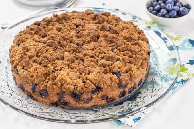 "A 9"" round blueberry buckle cake with a thick browned sugar streusel dotted with blueberries around the bottom sitting on a crystal glass plate"