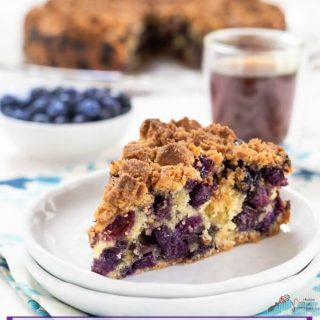A slice of blueberry buckle showing big berries throughout and topped with an oven-browned streusel topping. The full buckle, a white bowl of blueberries, and a cup of coffee are in the background.