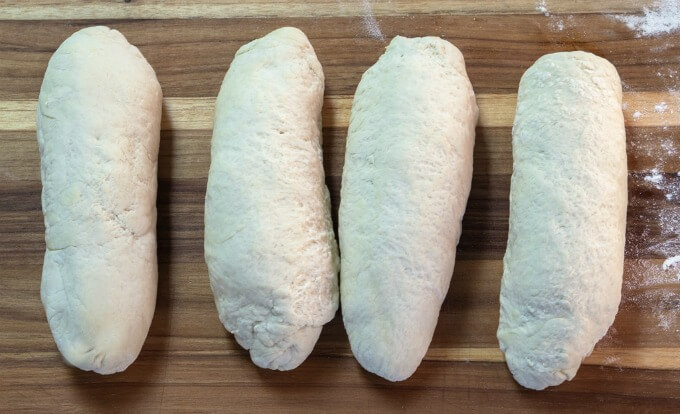Ciabatta bread dough rolled in torpedo-shaped rolls.