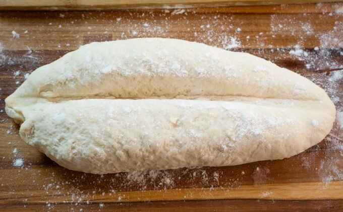 Rolls are shaped into a short baguette and then creased down the center