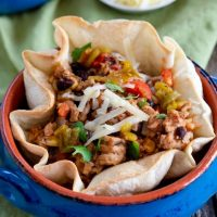 Green Chili Pork, corn, black beans and rice inside a tortilla bowl garnished with cheese