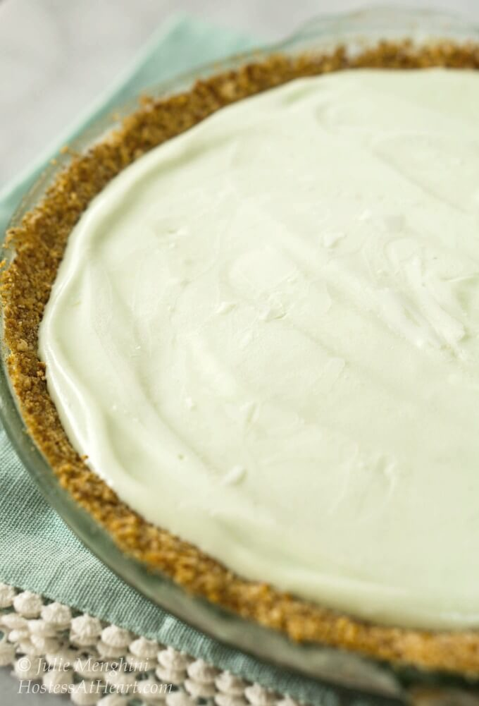 3/4 photo of an uncut Magic Margarita Pie with green tinted whipped topping filling sitting in a crunchy pretzel crust