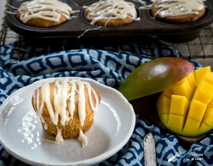 Mango muffin flavored with cream cheese and a vanilla bean drizzle sitting on a plate next to a diced mango over a blue patterned napkin. A full muffin tin sits in the background.