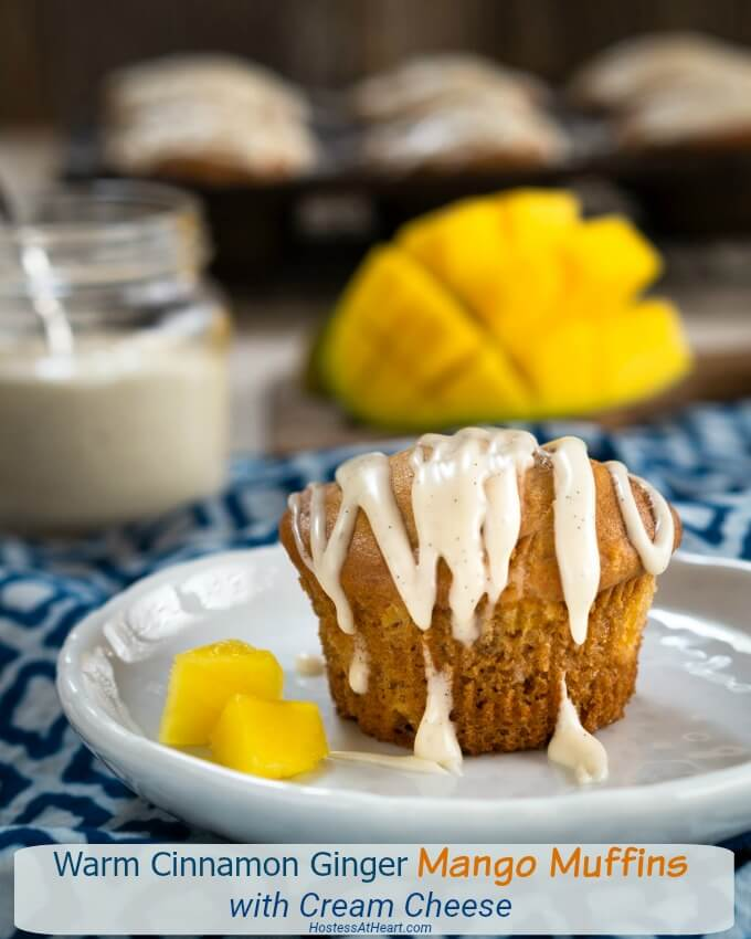 Mango muffin drizzled with vanilla bean glaze on a plate with two pieces of mango.
