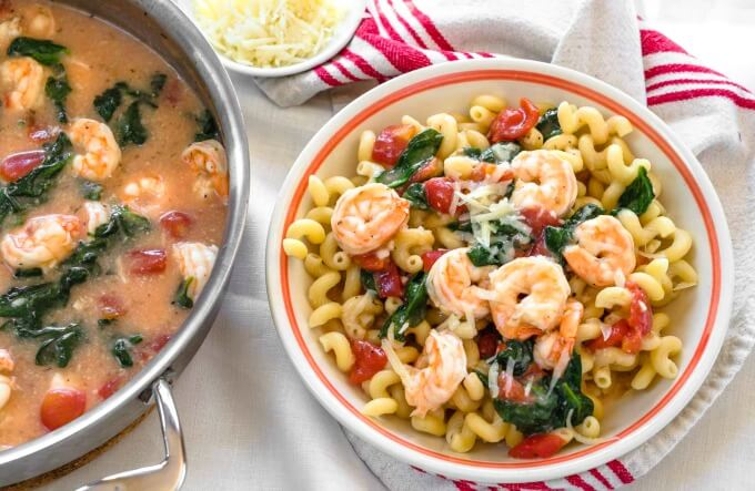 Top view of a bowl of Cavatappi pasta topped with cooed shrimp, spinach, tomatoes and grated cheese
