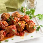 White platter with mexican flavored meatballs in a red chipotle sauce garnished with cilantro