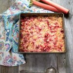 cake pan filled with bright red rhubarb dessert with a crumbled streusel topping surrounded by a multi-colored napkin and fresh rhubarb.