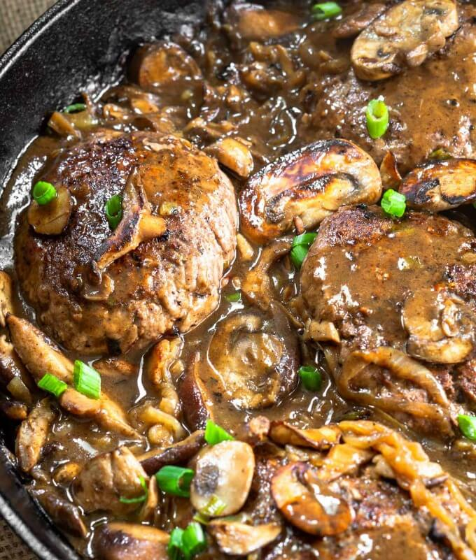 A Cast Iron Skillet full of Hamburger Steaks slathered in mushroom onion gravy and garnished with green onion