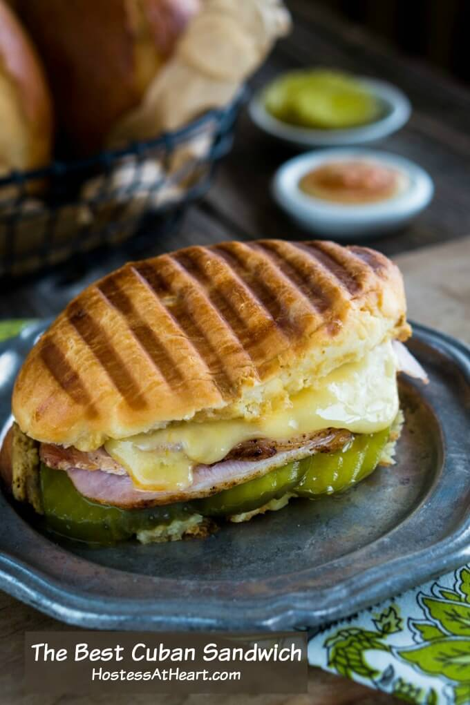 Oval Medianoche bread roll filled with dill pickle slices, ham, roasted pork, and swiss cheese on a grey metal plate. A white dish of a sriracha aioli sits in the background next to a basket of rolls.
