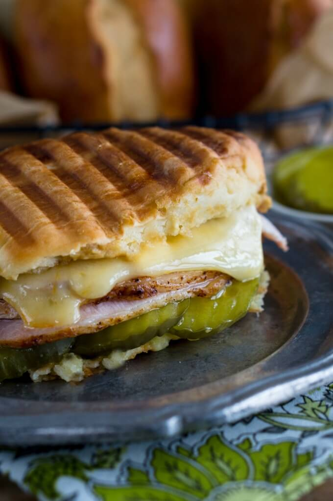 Close up of half a grilled bread roll filled with pickles, ham, roasted pork, and swiss cheese on a metal plate.
