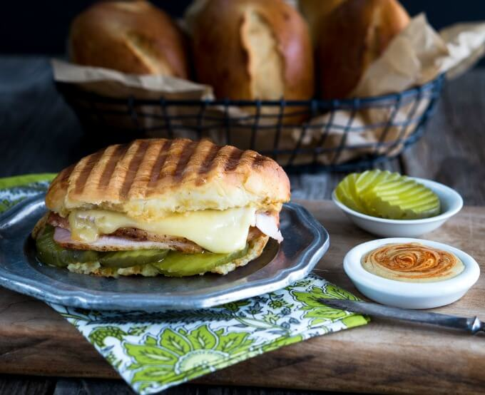 Oval Medianoche bread roll filled with dill pickle slices, ham, roasted pork, and swiss cheese on a grey metal plate and then grilled. White dishes of a sriracha aioli and pickle slices sit next to a basket of Medianoche rolls.