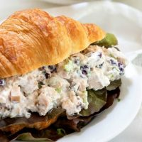 Croissant sandwich stuffed with chicken salad loaded with craisins, celery and green onion