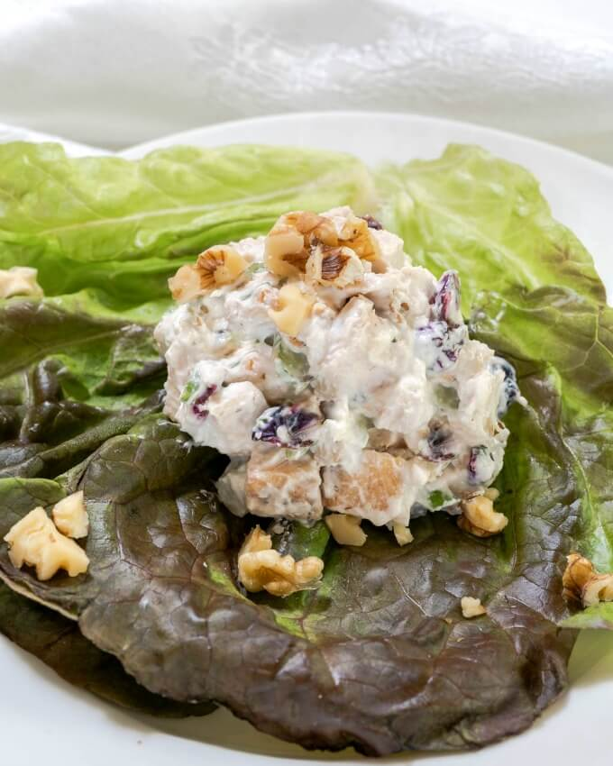 Scoop of Chicken Salad on a bed of lettuce and topped with chopped walnuts.