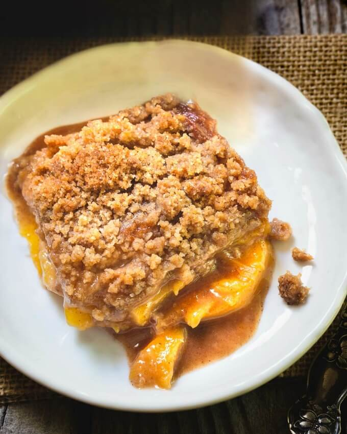 Top view of a serving of peach crisp with sauce and extra warm peaches spreading out on a white plate