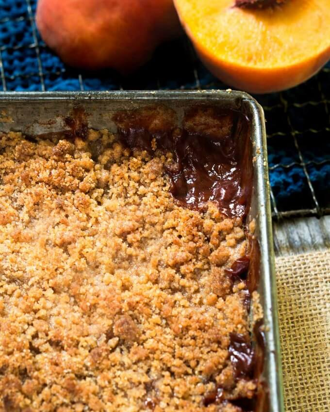 top view of a pan of peach crisp surrounded with a brown sugar cinnamon sauce and topped with a crunchy streusel in front of fresh peaches.