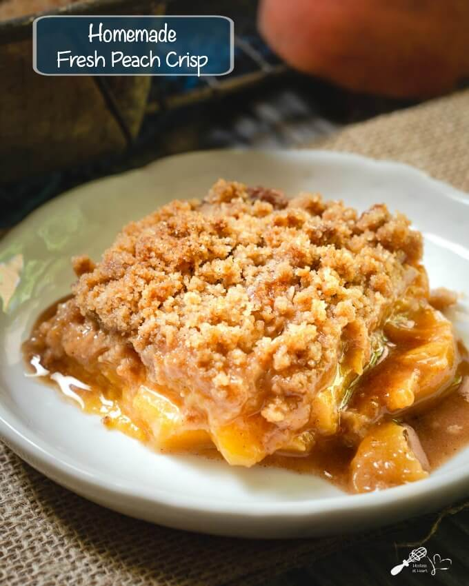 Peach crisp with a crunchy streusel topping sitting on a white plate and the pan in the background