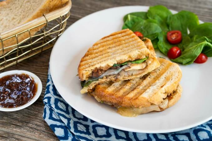 Grilled Cheese panini sandwich cut in half next to a spinach tomato salad on a gray plate