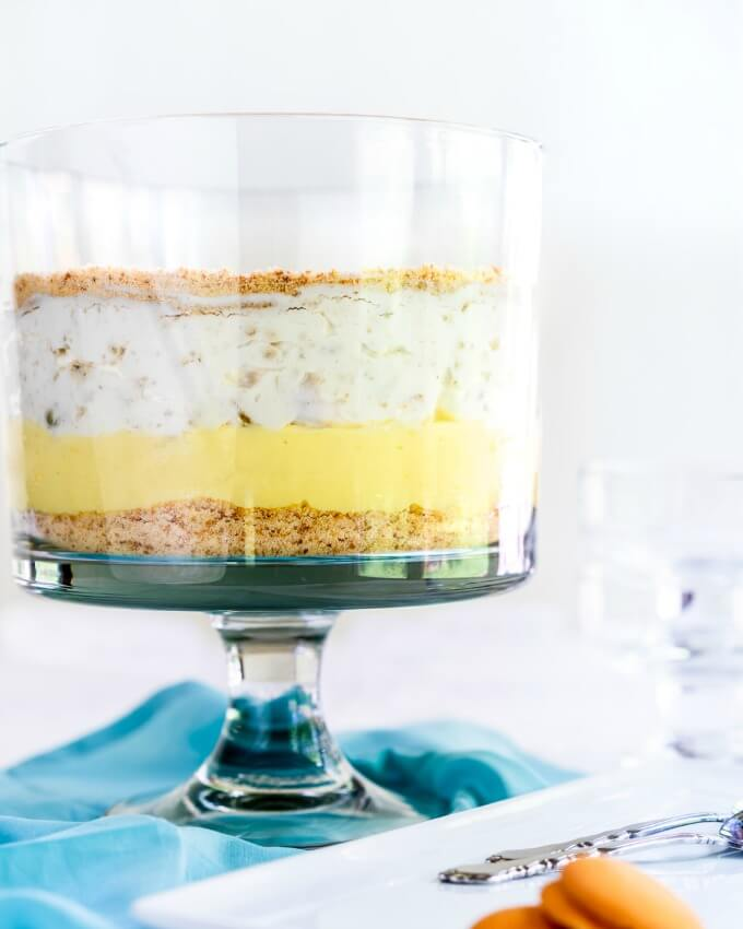 Side view of a trifle bowl filled with layers of ground cookies, pudding and fruit filled whipped topping on a blue napkin.