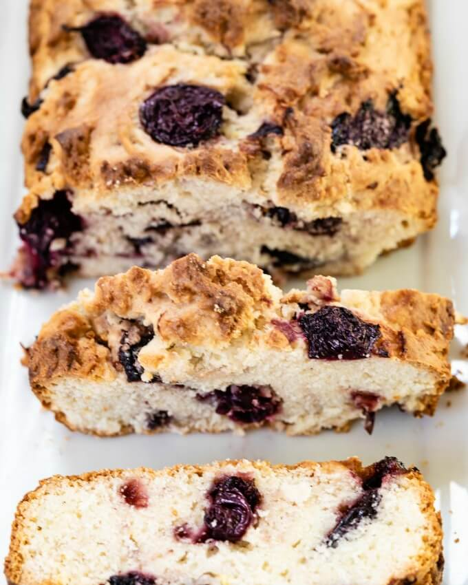 Top-down view photo of a sliced loaf of Cherry Quick bread sitting on a white plate.