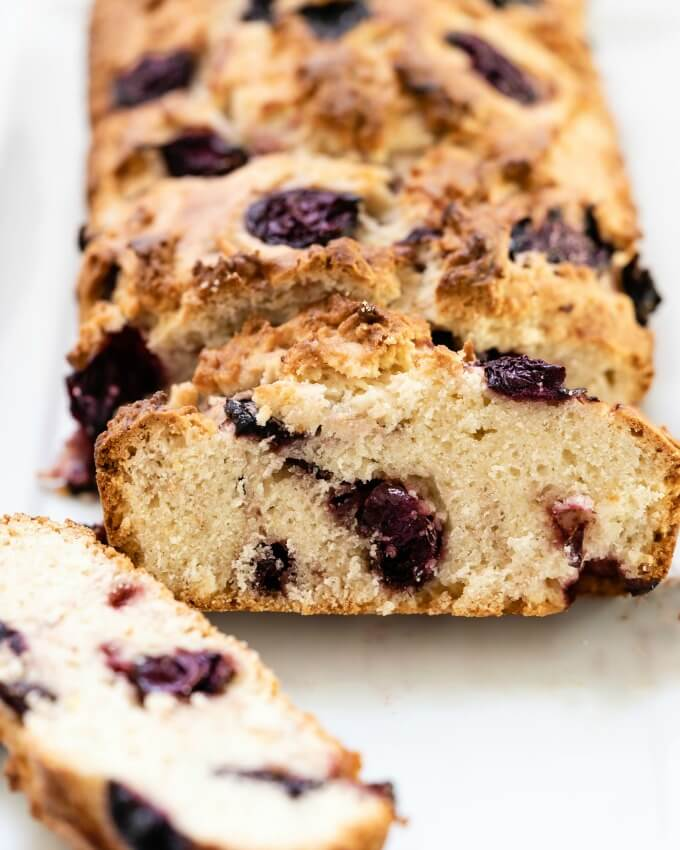 Close up of a slice of quick cherry bread loaded with dark purple cherries.