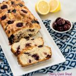 Cherry Bread loaf on a white plate sitting on a blue napkin next to lemons and cherries