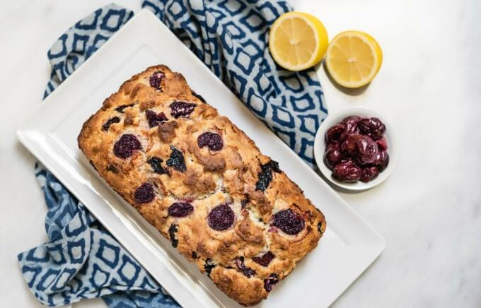 A top-down loaf of cherry bread sits on a white plate over a blue patterned plate. A small white bowl of cherries and to half lemons sit next to the plate.