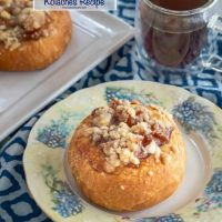 A browned kolache roll filled with baked apples and topped with a cinnamon crumble sitting on a floral plate and blue napkin. A cup of coffee and a tray of rolls sit behind it.