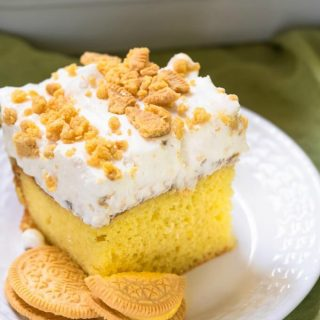 Bright yellow slice of cake with whipped topping and crushed cookies on a white plate with two broken cookies sitting on the same plate.