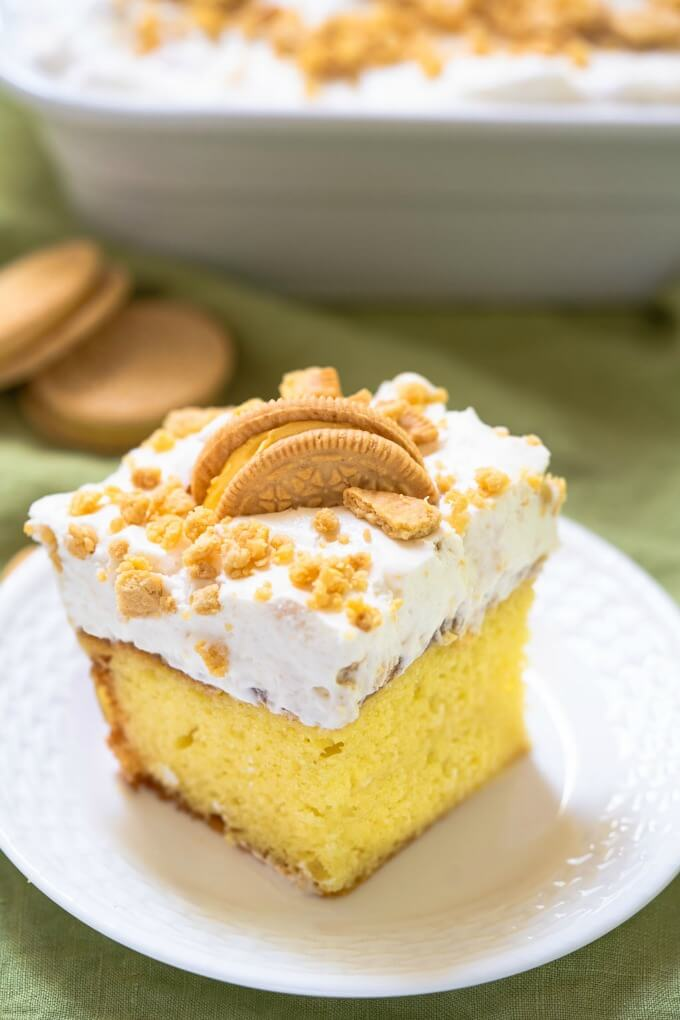 Slice of yellow lemon cake topped with white whipped topping, crushed cookies and a half cookie on a white plate. A white baking dish and whole cookies sits behind it.