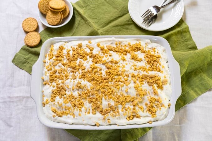 White pan of cake with whipped topping and lemon cookes crushed on top surrounded by whole cookies and empty white plates topped with forks all on a green napkin.