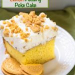 "Bright yellow slice of cake with a whipped cream topping sprinkled with crushed lemon cookies on a white plate. The title ""Lemon Pudding Poke Cake"" runs across the top."