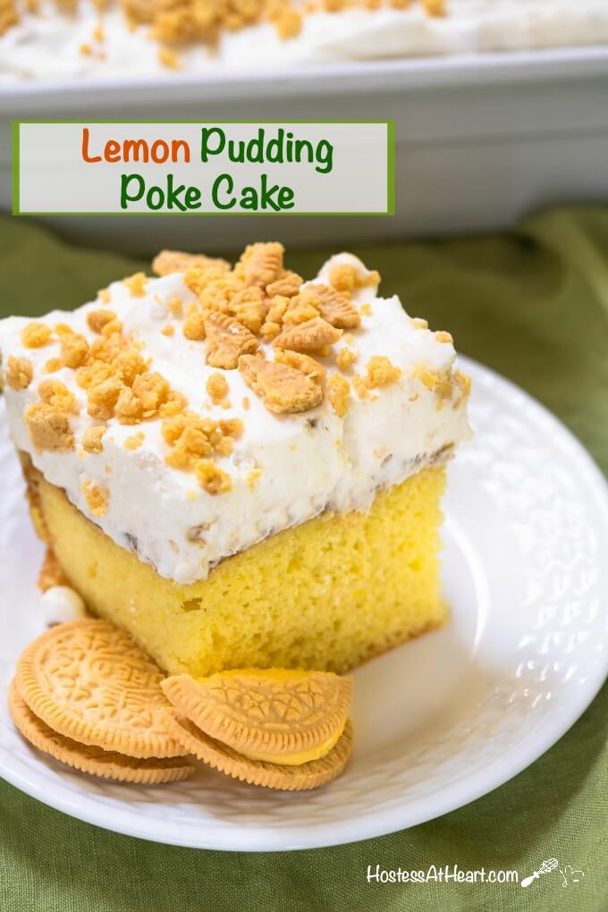 "Bright yellow slice of cake with a whipped cream topping sprinkled with crushed lemon cookies on a white plate. The title ""Lemon Pudding Poke Cake\"" runs across the top."