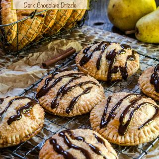 A baking rack topped with 6 pear hand pies baked brown and drizzled with chocolate. A basket of more pies and raw pears sit in the background.