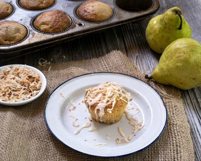 Single muffin topped with coconut on a white plate surrounded by fresh pears, coconut in a bowl and a tin of muffins