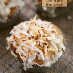 Top shot of a muffin in a silver paper topped with toasted coconut with two muffins in the background