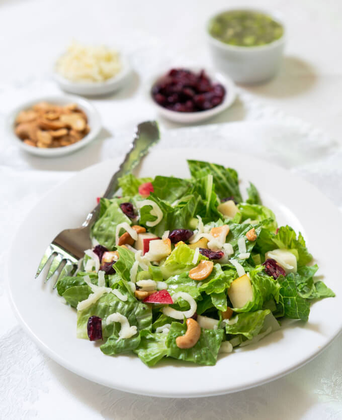 Angled photo of a green salad topped with apples, pears, cheese, cashews and craisins. Small white bowls hold extra dressing, cashews, cheese and craisins behind the salad bowl.