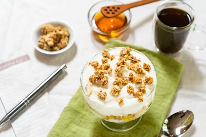 A table set with yogurt topped with granola on a green napkin next to a coffee cup, spoon, dish of granola and a shopping list topped with a pen.