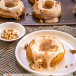 Donut with glaze and pecan pieces sitting on a white plate on a stripped towel. A pan of donuts and a dish of pecans sit behind it.