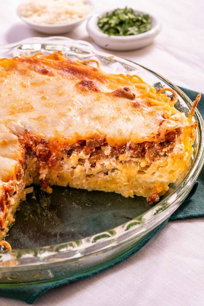 A pie plate with baked spaghetti pie with a cut piece removed showing layers of pasta, meat sauce and mozzarella.