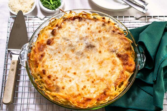 A pie plate full of spaghetti pie and baked brown. It's sitting on a cooling rack next to a green napkin and pie server.