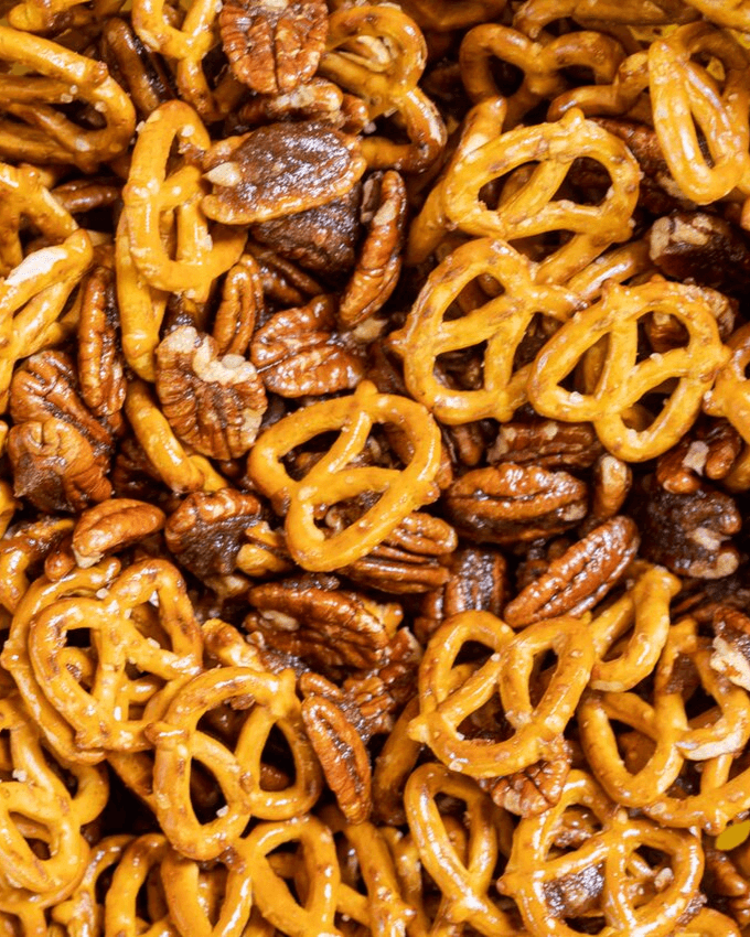 Close up of pretzels and pecans mixed with melted butter and brown sugar.