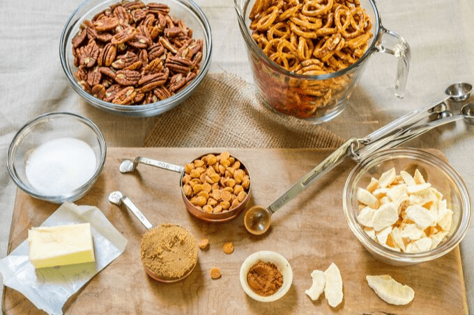 Ingredients of Apple Pie Snack mix including pretzels, pecans, dried apples, brown sugar, cinnamon, butter and caramel chips