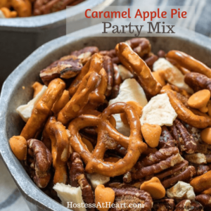 Close up view of pretzels, pecans, caramel chips and dried apples mix in a bowl on a blue striped napkin