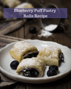 The blueberry puff pastry rolls on a white plate with the title of the recipe printed on top third of the photo