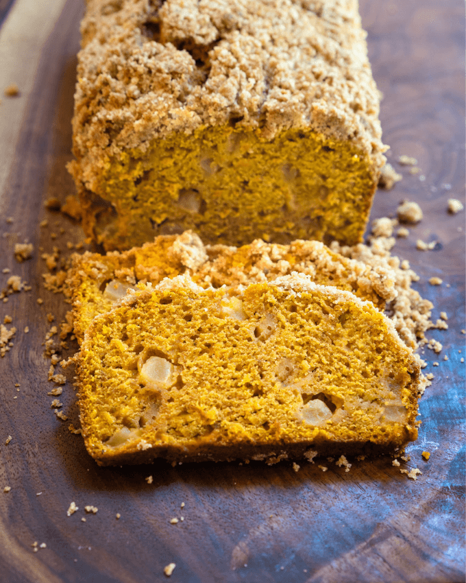 Slice loaf of pumpkin bread dotted with chunks of apple and topped with streusel topping sitting on a wooden cutting board