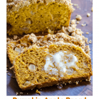 A slice of pumpkin bread dotted with chunks of apple and streusel topping with melted butter running down the slice over a wooden cutting board.