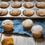 Angle view of pumpkin muffins sitting on a blue napkin and wooden board in front of a tin of muffins.