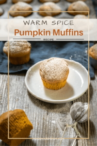 Angle photo of a powder sugar dusted pumpkin muffin sitting on a white plate surrounded by other muffins in front of a tin of muffins.