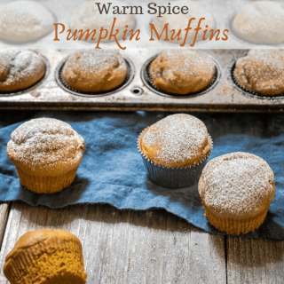 "FAngle view of mini pumpkin muffins dusted with powdered sugar sitting on a blue napkin and wooden board in front of a tin of muffins. The title ""Warm Spice Pumpkin Muffins"" runs across the top of the photo."